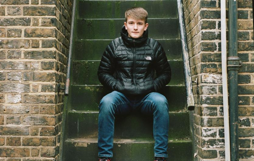Teenage boy sitting on steps, looking intently at camera, hands in pockets