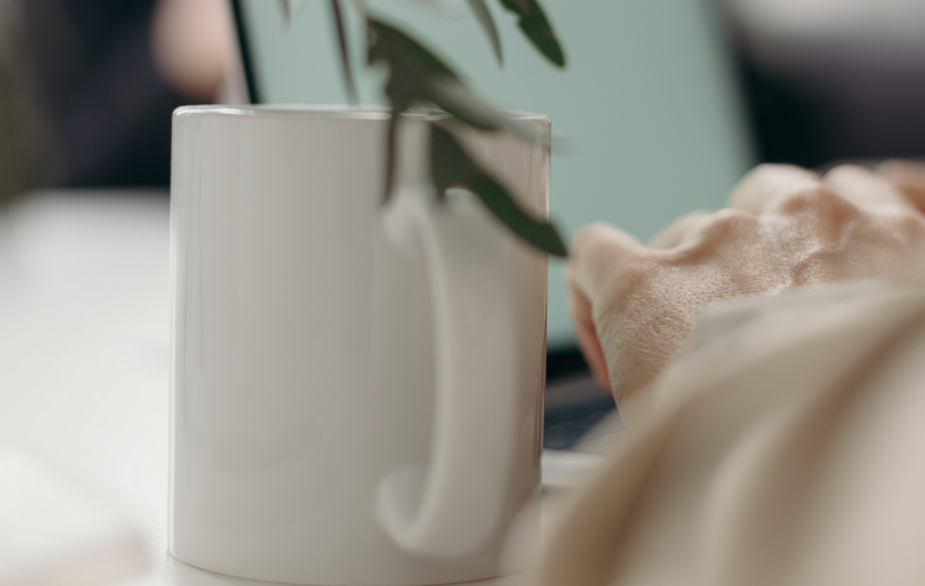An arm with a mug next to it, beside a laptop and a houseplant