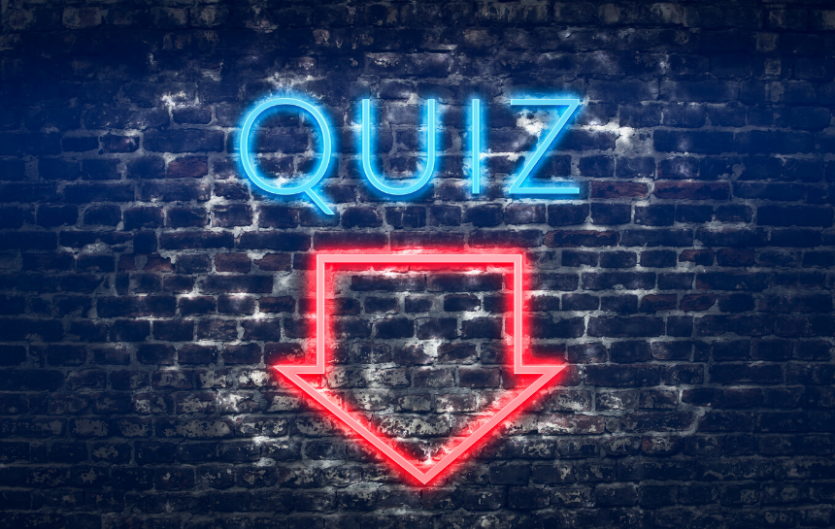 Neon sign saying 'Quiz' with an arrow pointing downwards
