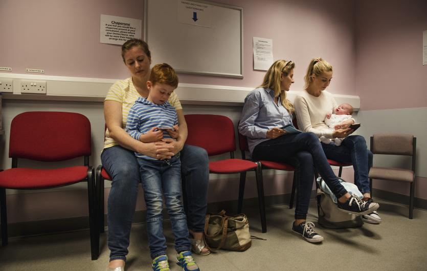 Mother with son in a clinic waiting room; therapist talking to another mother with a baby