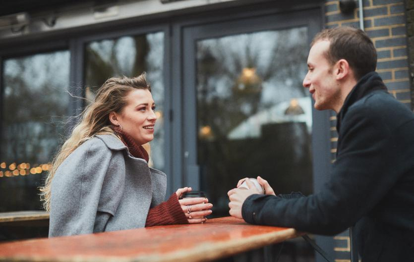 A man and woman chatting over a coffee.