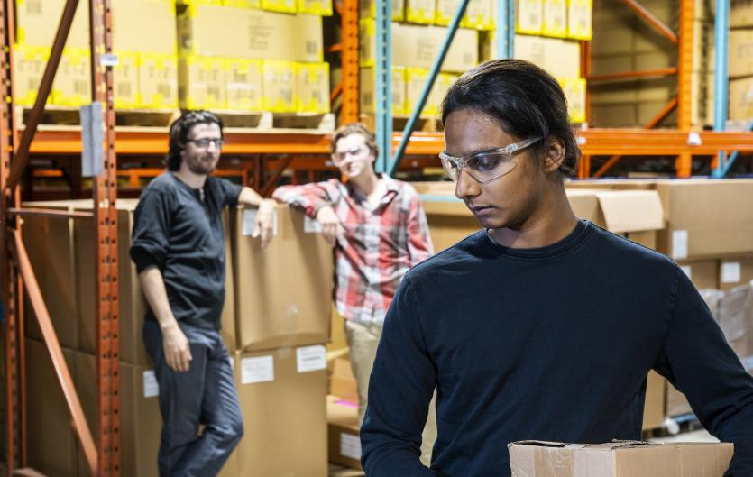 A warehouse employee being watched and possibly laughed at by colleagues